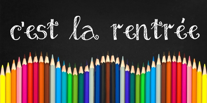 C'est la rentree (meaning Back to schoo in french) written on a black board background with a wave of colorful wooden pencils