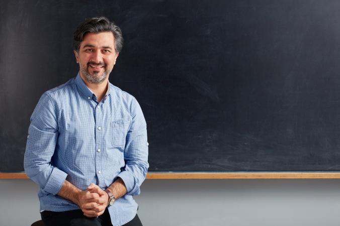Teacher posing on blackboard.